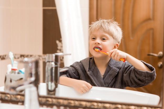 Jongen in de ochtend zijn tanden poetsen in de badkamer