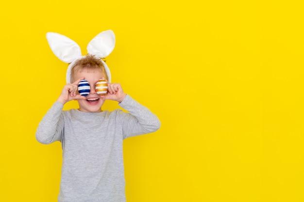 Jongen in de oren van het konijnkonijntje op hoofd met gekleurde eieren op geel
