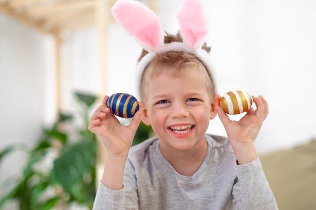 Jongen in de oren van het konijnkonijntje op hoofd met gekleurde eieren thuis