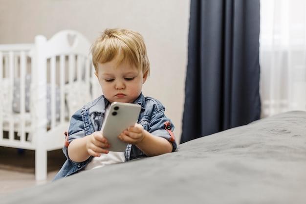 Jongen in de slaapkamer met behulp van mobiele telefoon