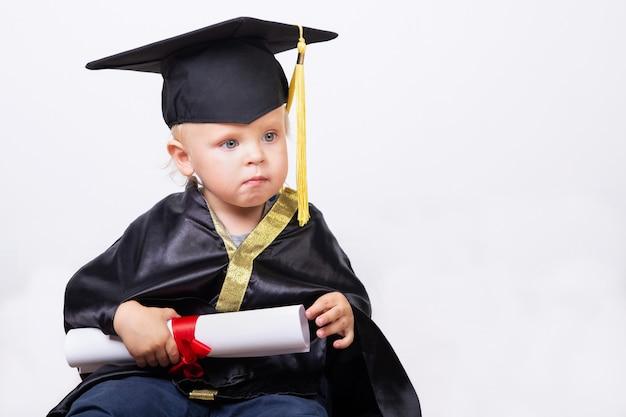 Jongen in een bachelor of master pak met diploma scroll geïsoleerd op een lichte achtergrond met kopie ruimte. vroege ontwikkeling, afstuderen, onderwijs, wetenschap, vroeg leren babyconcept