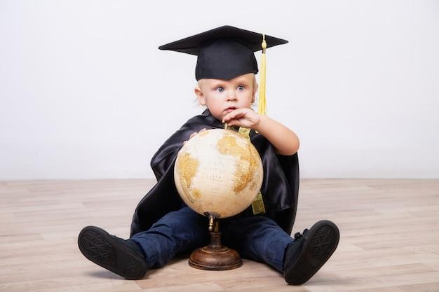 Jongen in een bachelor of master pak met een wereldbol op een lichte achtergrond. vroege ontwikkeling, afstuderen, onderwijs, wetenschap, vroeg leren babyconcept