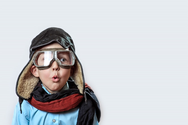 Jongen in een blauw shirt, pilotenbril, muts en sjaal