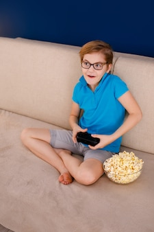 Jongen in een blauw t-shirt en een grote bril op de bank zitten, popcorn eten en thuis spelen met een gamepad. blauwe achtergrond en vrije ruimte voor tekst. onderwijs thuis en op afstand