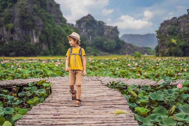 Jongen in een geel op het pad tussen de lotusmeer mua-grot ninh binh vietnam vietnam heropent na