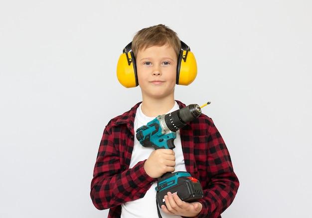 Jongen in een helm speelt in de bouwer met gereedschap. geïsoleerd