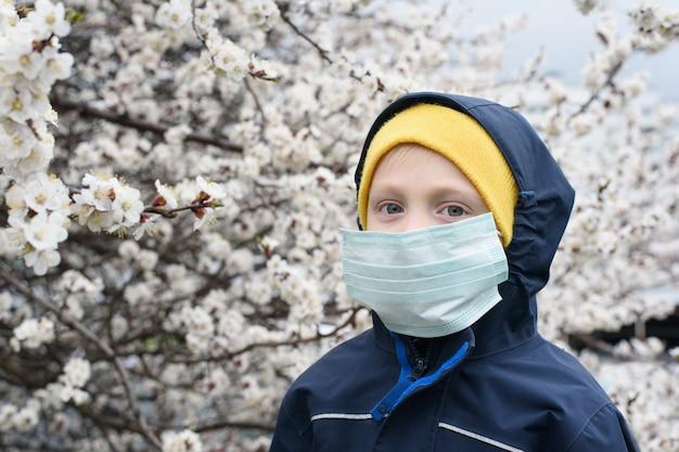 Jongen in een medisch beschermend masker buitenshuis