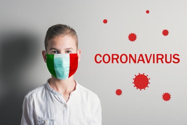 Jongen in een medisch masker met vlag van italië op zijn gezicht op lichte achtergrond.