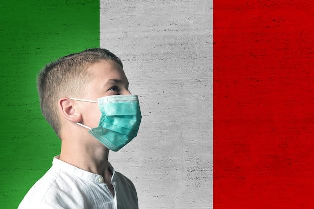 Jongen in een medisch masker op zijn gezicht op de achtergrond van de vlag van italië.
