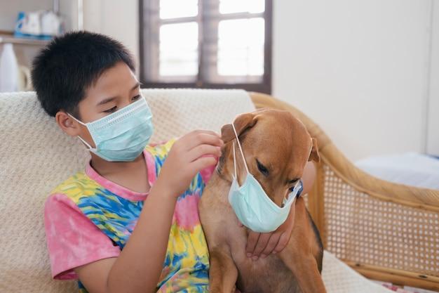 Jongen in een medisch masker zet een medisch masker op zijn hond.