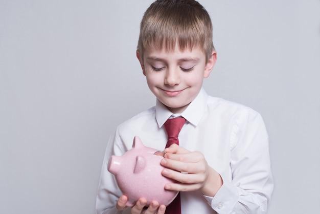 Jongen in een overhemd en das legt een munt in een roze spaarvarken. bedrijfsconcept.