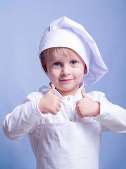 Jongen in een pak en chef-kok glimlacht