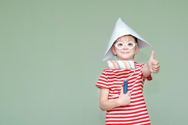 Jongen in een papieren hoed en bril toont de koelte. portret. roller voor het schilderen