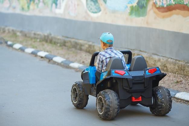 Jongen in een pet rijdt een auto in een park op een zomerdag