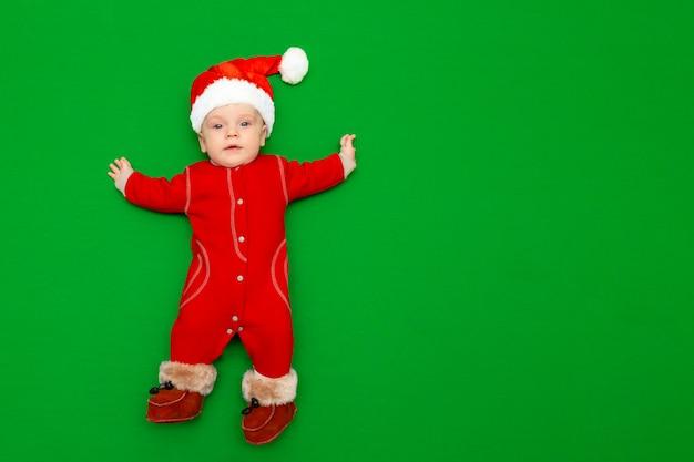 Jongen in een rood kerstmankostuum, bontlaarzen en een kerstmuts