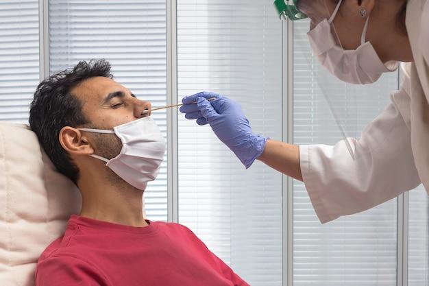 Jongen in een rood shirt en masker zit terwijl een verpleegster met anti-covid-19 bescherming de pcr-test doet