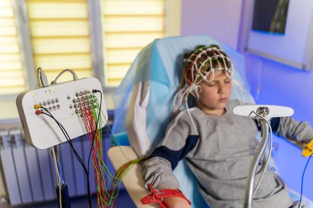 Jongen in een speciale medische pet tijdens elektro-encefalografie naast de monitor met metingen.