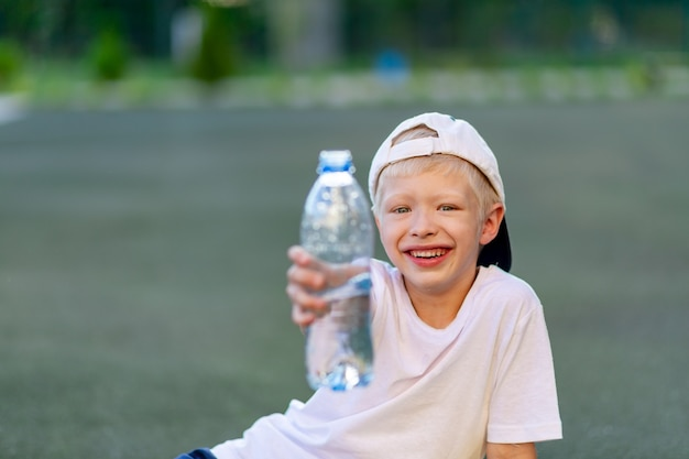 Jongen in een sportuniform zittend op een groen gazon op een voetbalveld en met een fles water