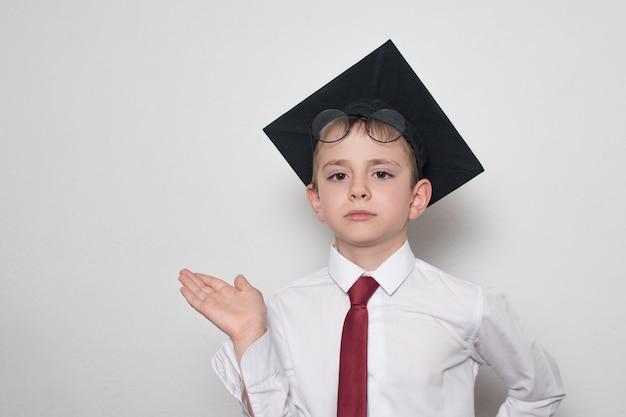 Jongen in een vierkante academische hoed en bril houdt zijn palm omhoog. school concept.