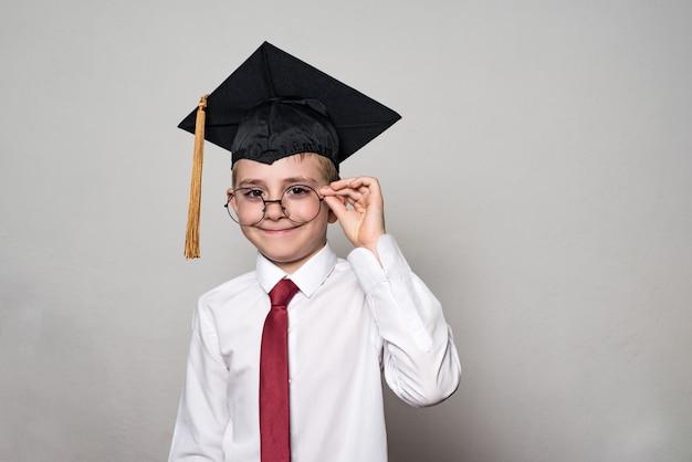 Jongen in een vierkante academische pet en wit overhemd corrigerende bril.