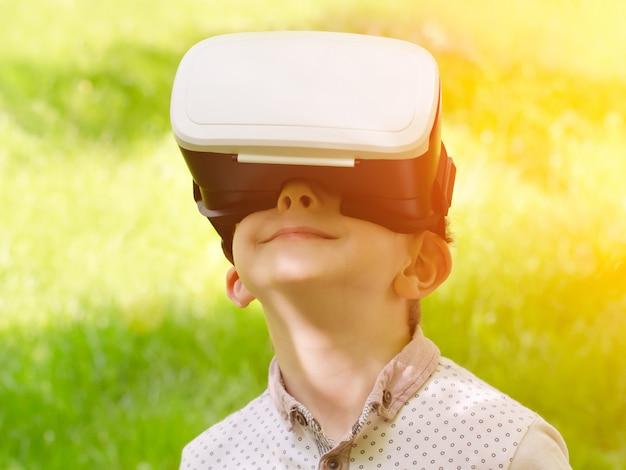 Jongen in een virtuele werkelijkheidshelm op een achtergrond van groen gras