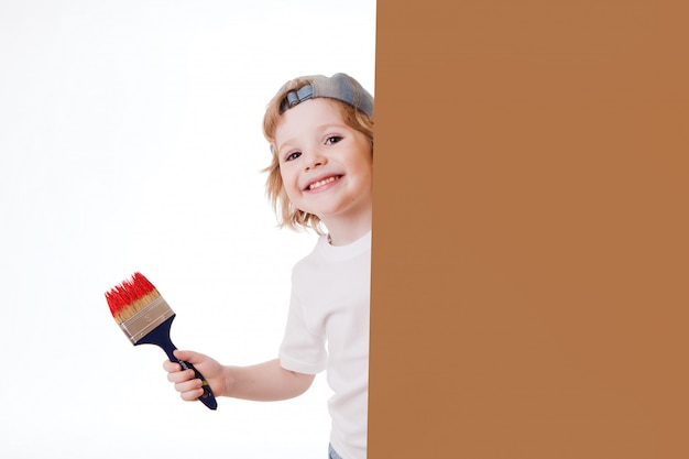 Jongen in een wit t-shirt met een penseel in zijn handen, schildert aan de muur, schrijft.