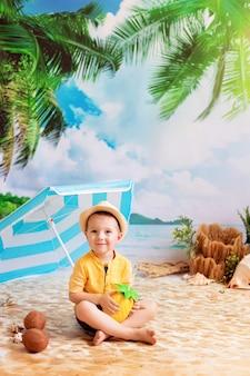 Jongen in een zwembroek zonnebaadt op een zandstrand met palmbomen aan zee onder een parasol