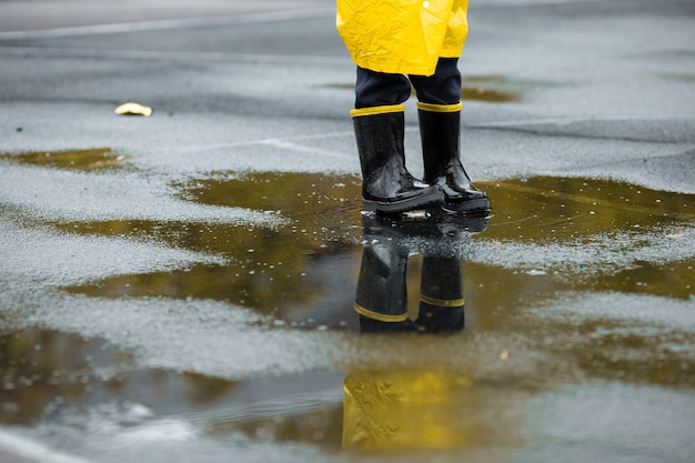 Jongen in gele waterdichte mantel en zwarte rubberen laarzen staan in een plas buiten in de regen in de herfst.