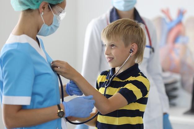 Jongen in gestreepte t-shirt luistert naar de hartslag van de arts met een zwarte stethoscoop