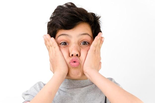 Jongen in grijze t-shirt die grappige gezichten maakt
