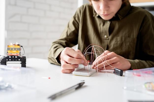 Jongen in groen shirt werkt met led-verlichting op experimenteel bord voor wetenschappelijk project