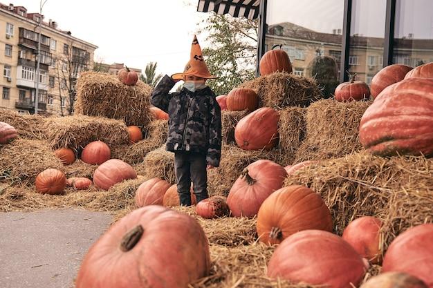 Jongen in halloween-kostuum met pompoenen op boerderijmarkt staat op hooi. enge decoraties. truc of traktatie voor kinderen. beschermend gezichtsmasker dragen op halloween 2020 tijdens covid-uitbraak. nieuw normaal.