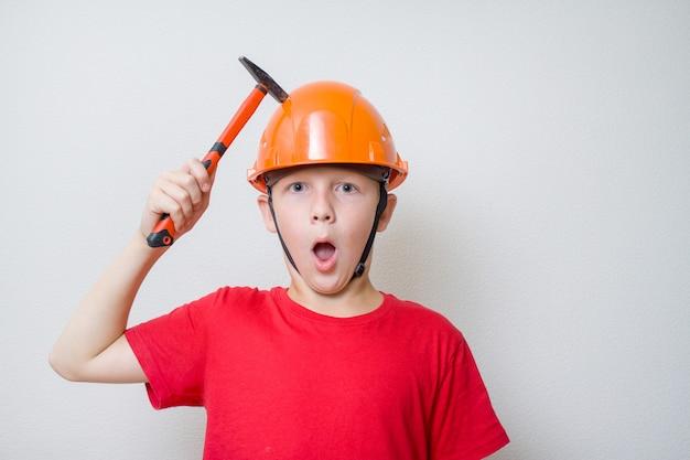 Jongen in helm, helm. jonge bouwer met hocked gezicht klopt met hamer op hoofd