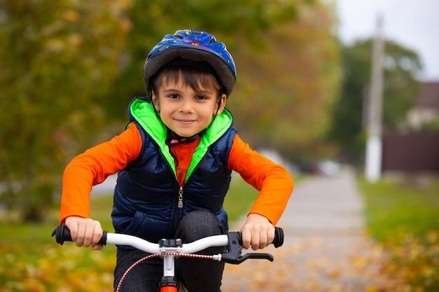 Jongen in het de herfstpark. klein kind dat een helm draagt en op een fiets rijdt op een herfstdag. actieve gezonde buitensporten.
