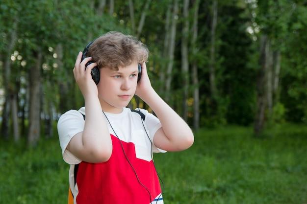 Jongen in hoofdtelefoon luistert naar muziek. tiener in koptelefoon in het bos