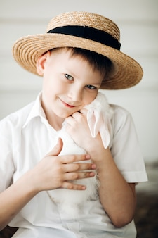 Jongen in hooihoed die leuk wit konijntje en het glimlachen houdt