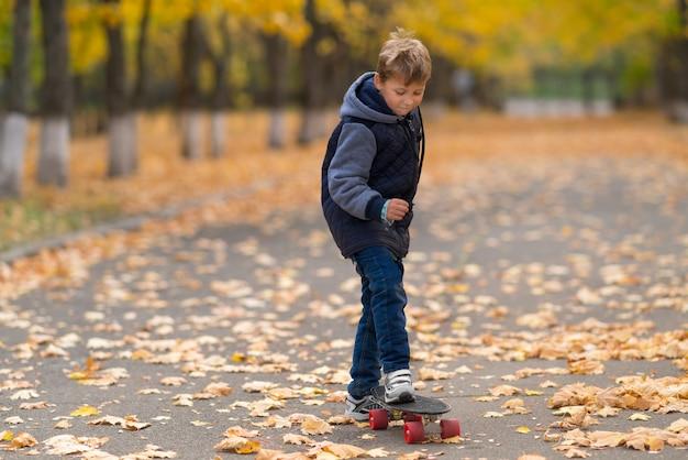 Jongen in jasje dat zich met één voet op skateboard bevindt, gaat vooruit. voorportret van volledige lengte in het park bedekt met gele bladeren.