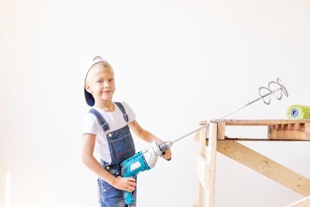 Jongen in jumpsuit met een bouwmixer Premium Foto