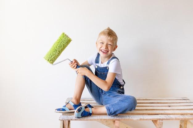 Jongen in jumpsuit schilderij roller te houden