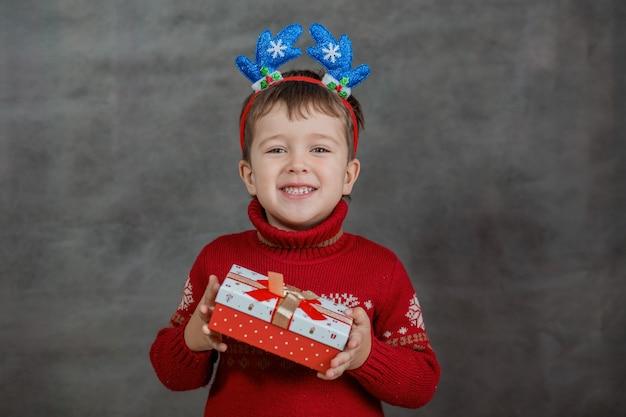 Jongen in kerstmissweater en rand van hertengewei met weinig kerstmisgift. hoge kwaliteit foto