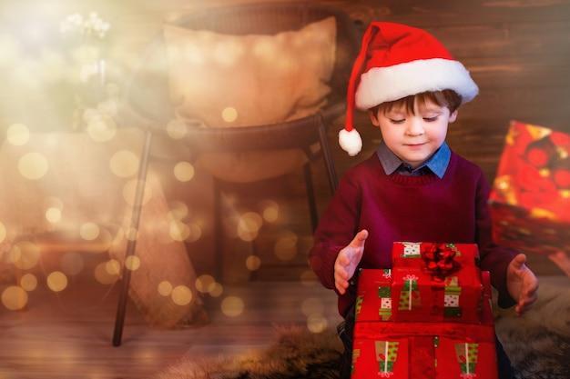 Jongen in kerstmuts geschenken openen