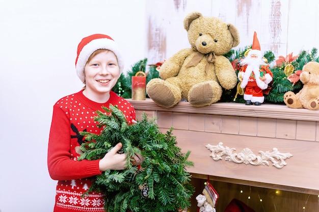 Jongen in kerstmuts versieren woonkamer en open haard voor kerstmis of nieuwjaar.