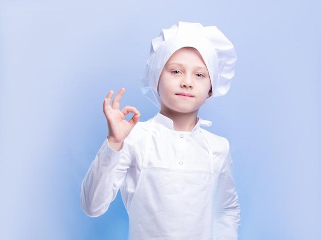 Jongen in kokskostuum en pet glimlacht en toont het ok-teken