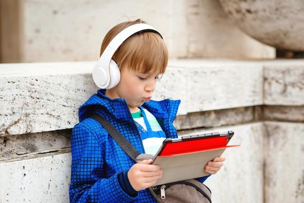 Jongen in koptelefoon tijdens het luisteren naar muziek na schoolstudies op straat.