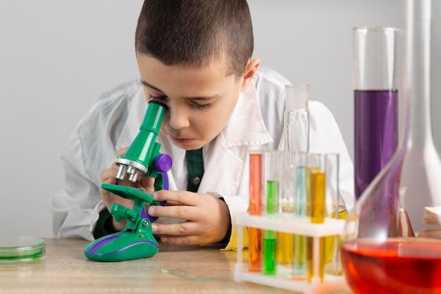 Jongen in laboratorium met microscoop