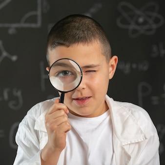 Jongen in laboratorium met vergrootglas