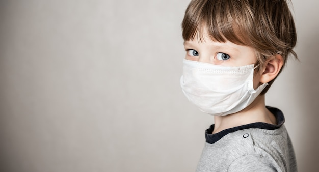 Jongen in medisch masker. coronavirus covid-19 lockdown, paniek. vaccin tegen nieuw virus
