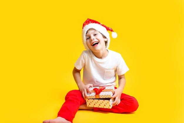 Jongen in pak van santas hoed op gele muur. concept kerst- en nieuwjaarsvakantie