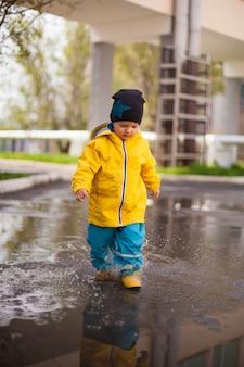 Jongen in plassen in een beschermend pak tegen water en rubberen laarzen op lente plassen.