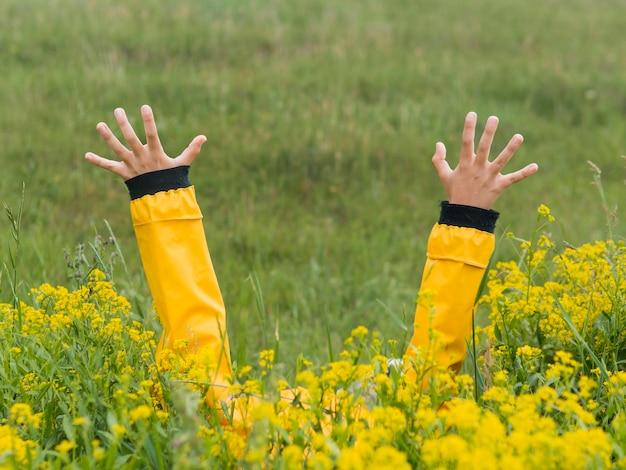 Jongen in regenjas handen in de lucht